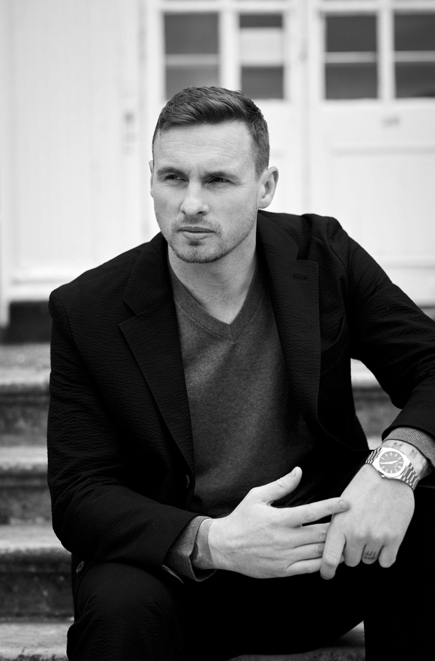David Stockdale sitting on some steps outside wearing a blazer
