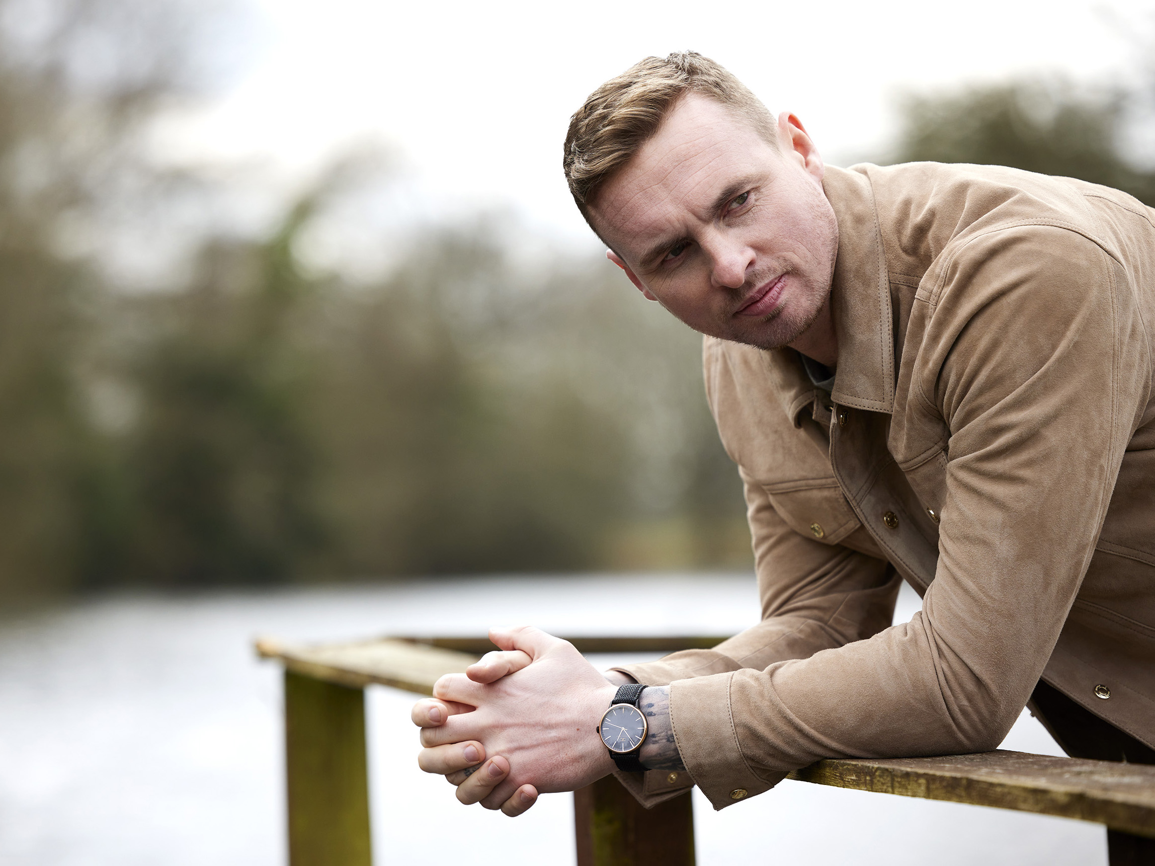 David Stockdale leaning on a wooden barrier by a lake