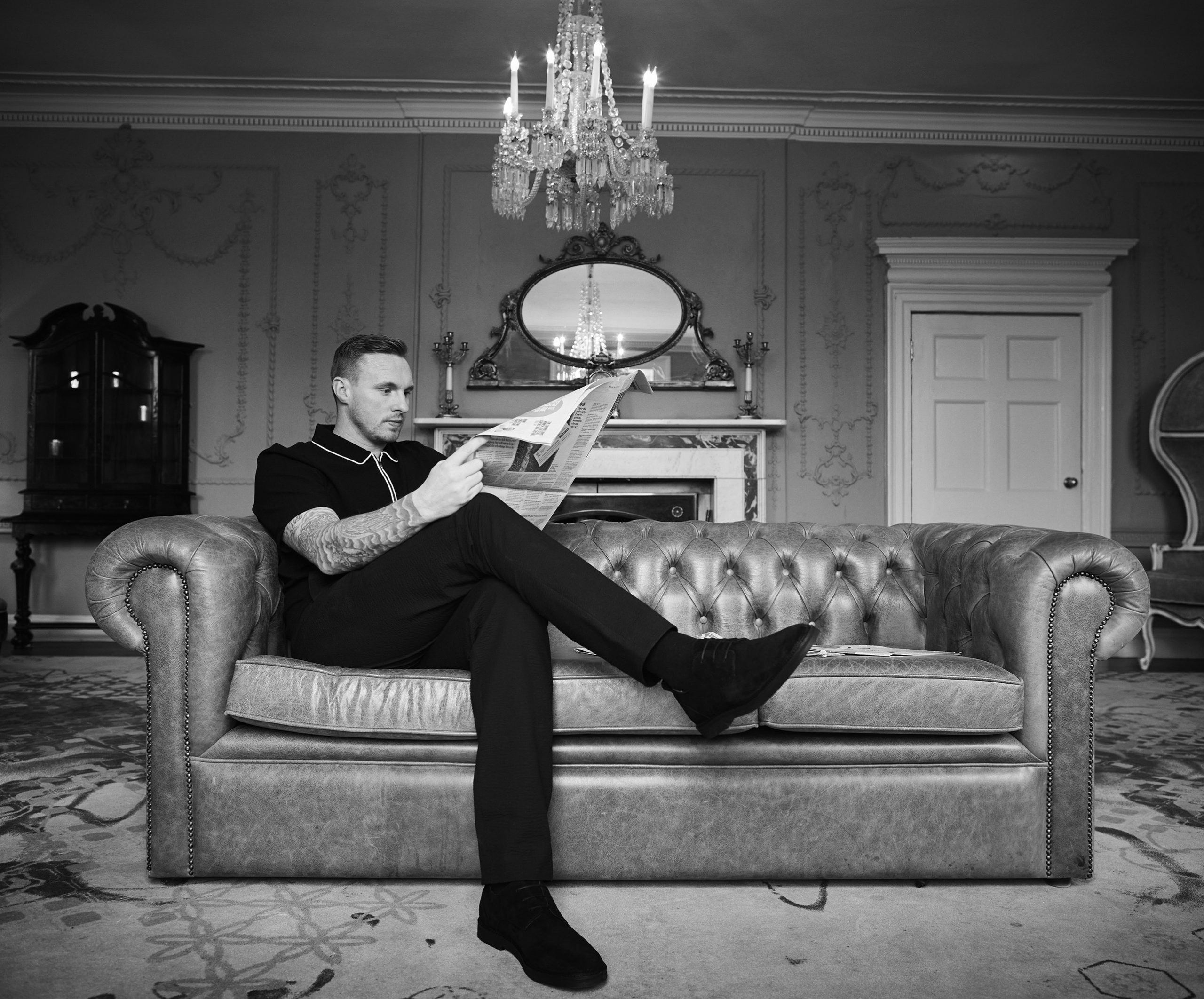 David Stockdale reading a newspaper whilst sat on a brown leather sofa
