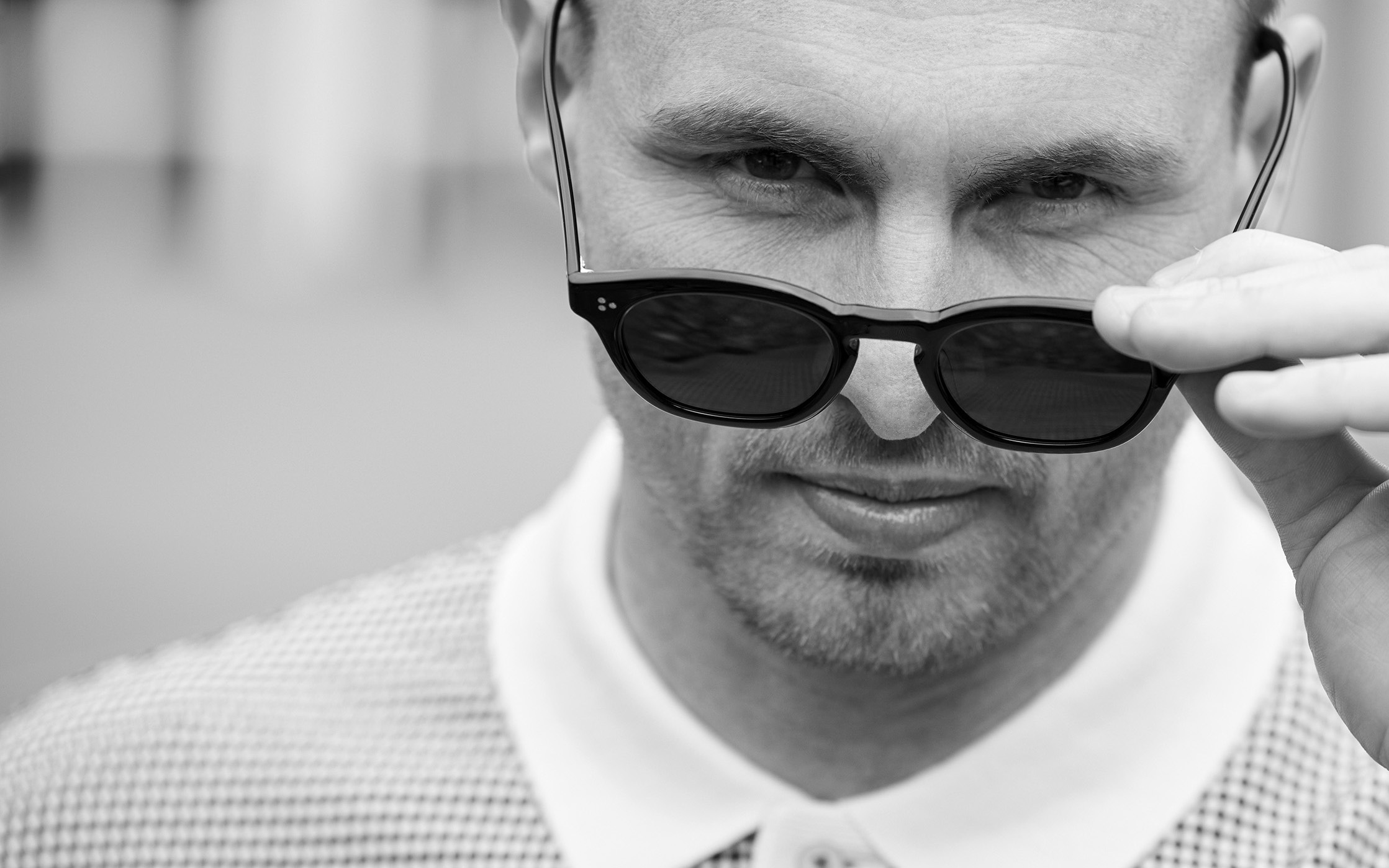 David Stockdale looking at the camera while holding a pair of sunglasses on the tip of his nose