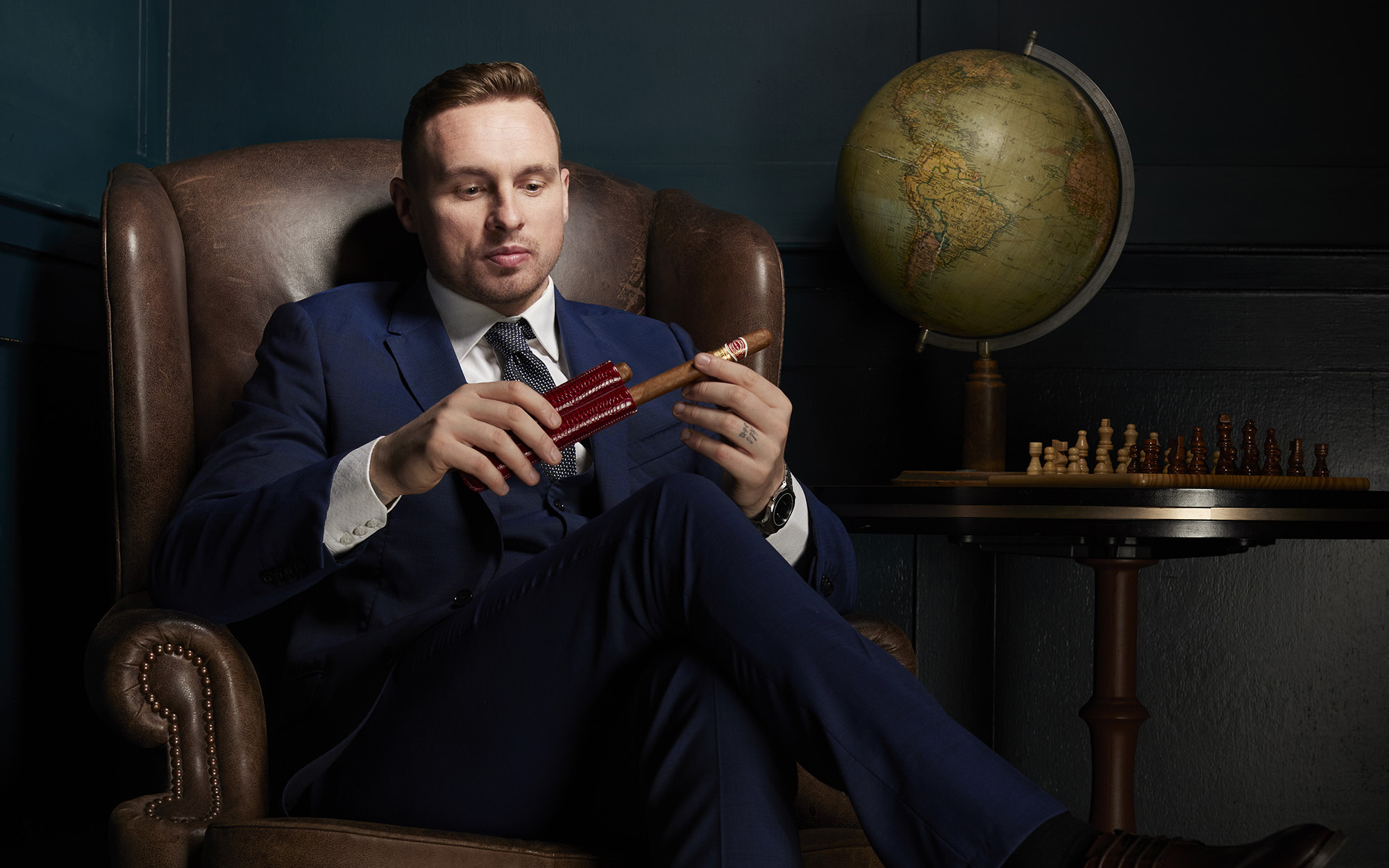 David Stockdale sat in a leather armchair wearing a blue suit holding a cigar