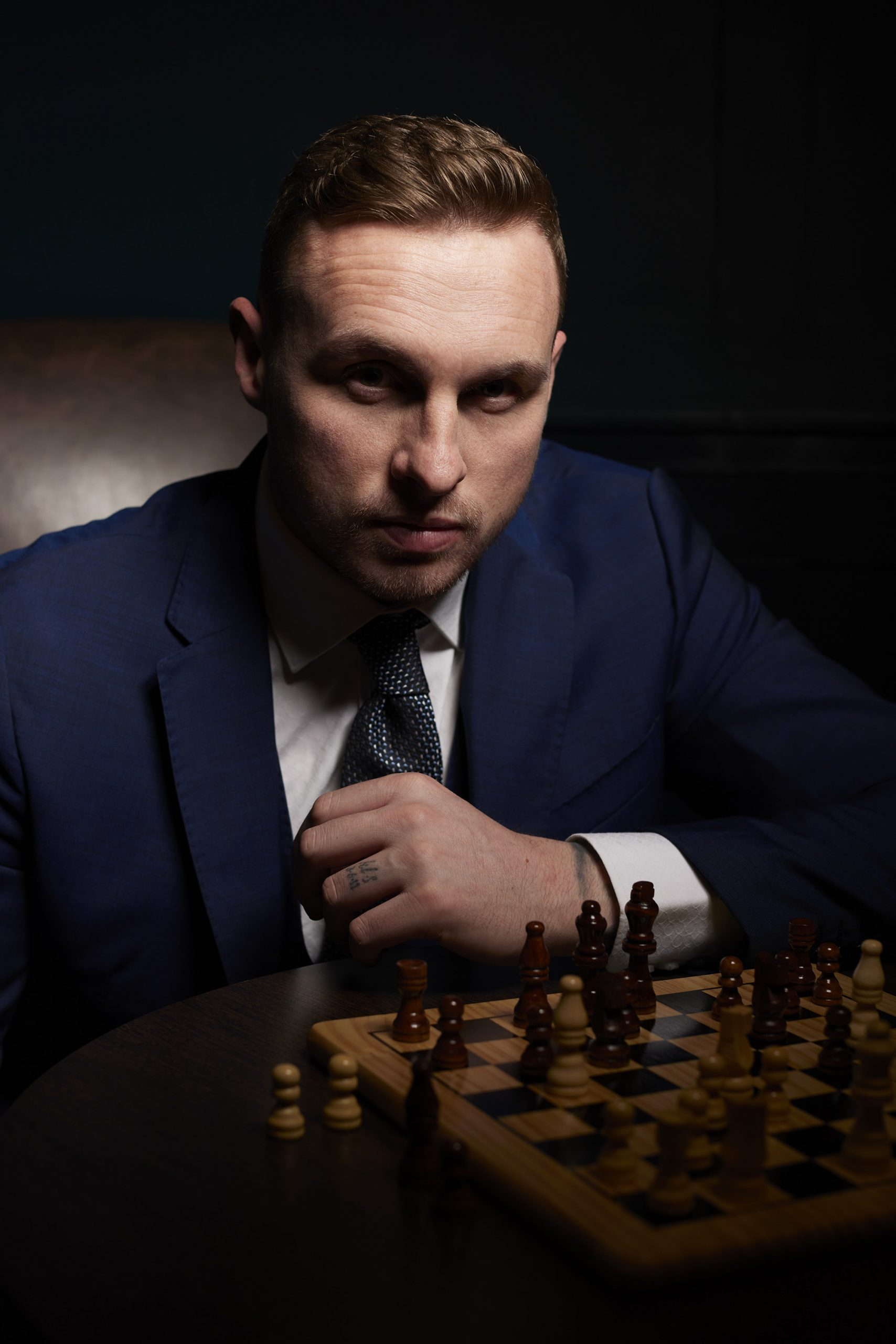 David Stockdale wearing a blue suit and playing chess