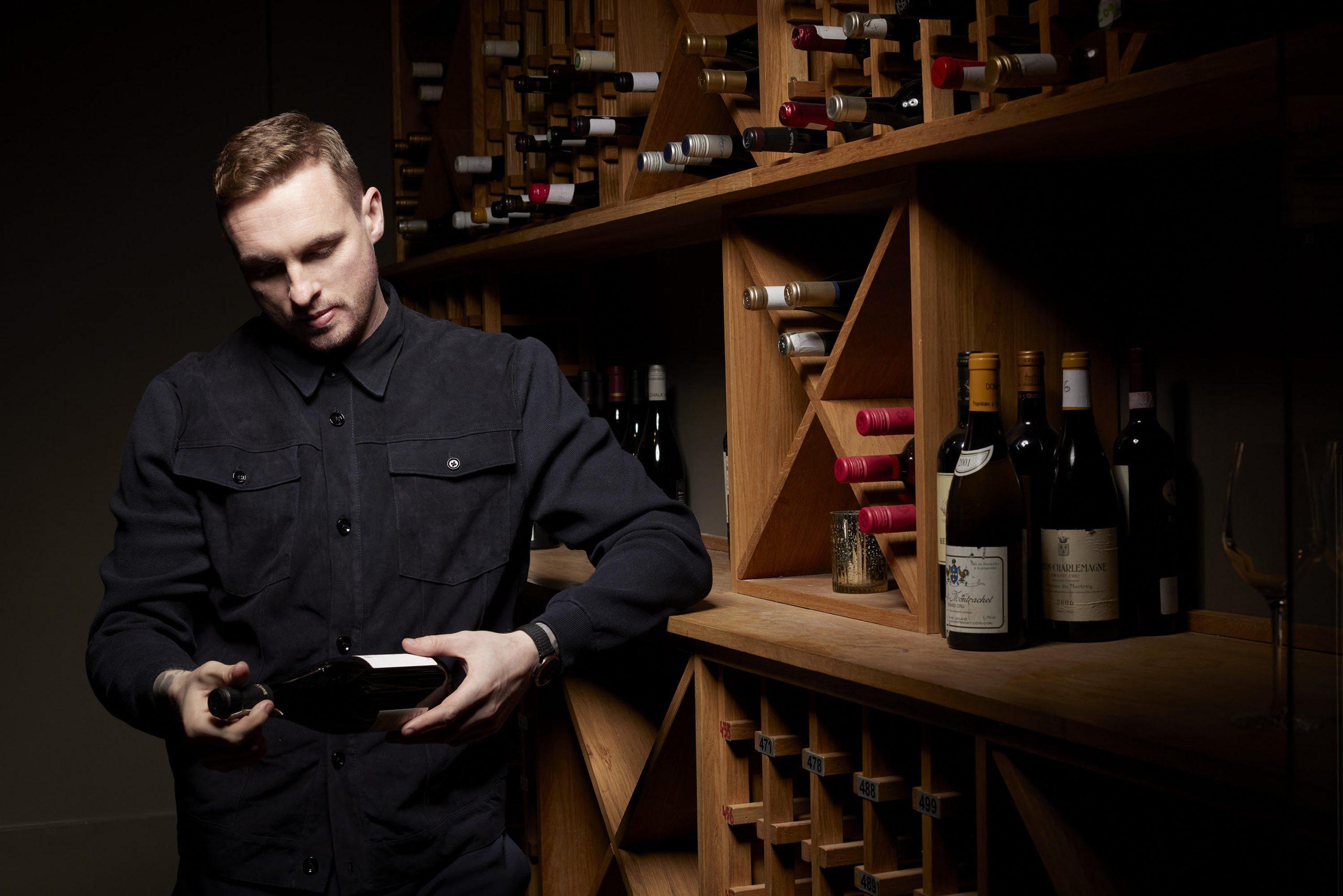 David Stockdale holding a bottle of wine in a wine cellar